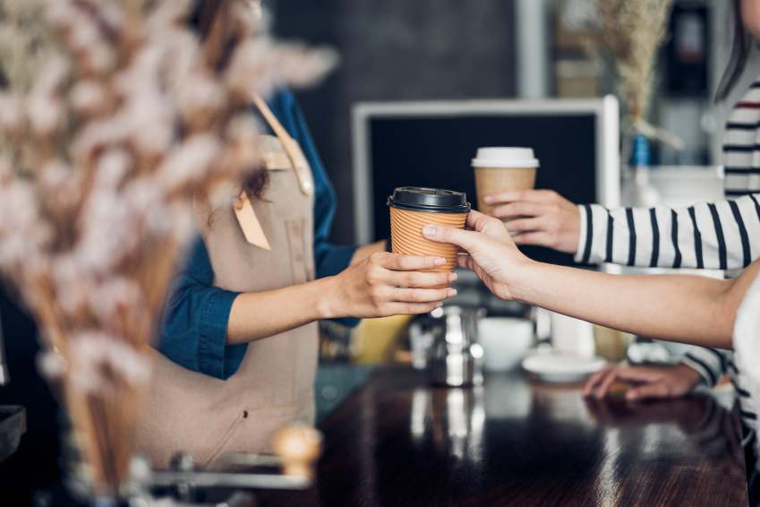 Flere hender som holder kaffekopper i papp over en kafedisk