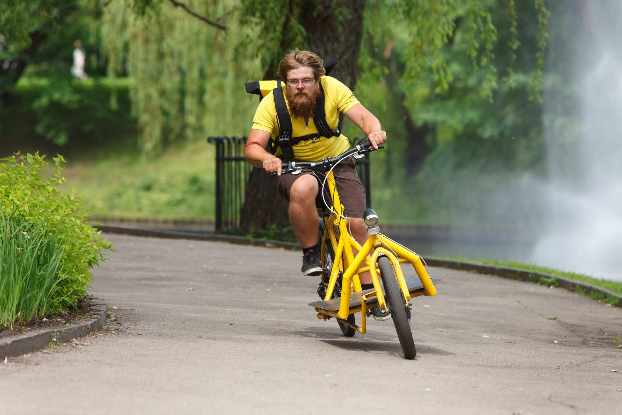 Mann som sykler gjennom en park på en gul elsykkel med lastebrett foran