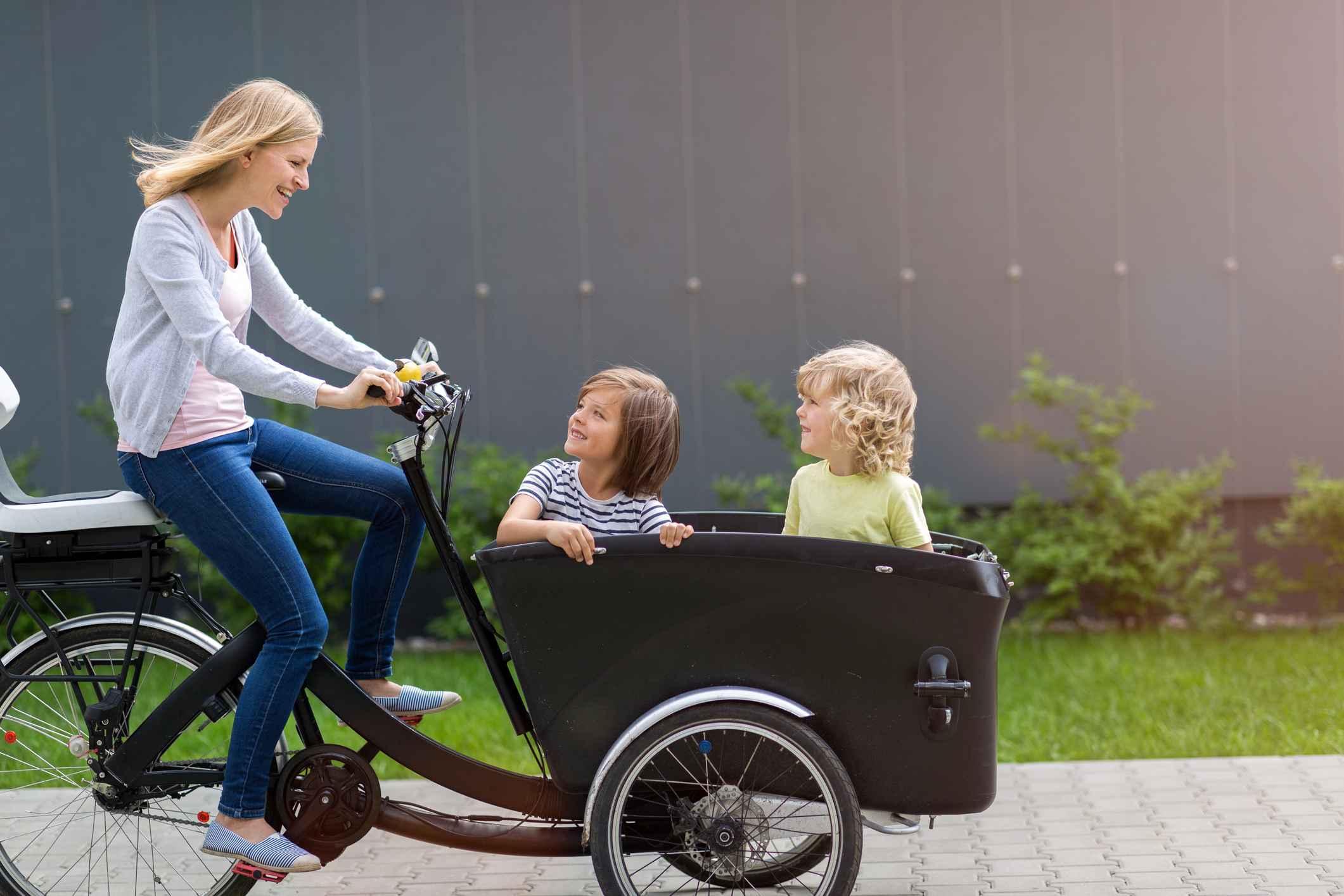 En mor som sykler på en lastesykkel med to barn som glade passasjerer