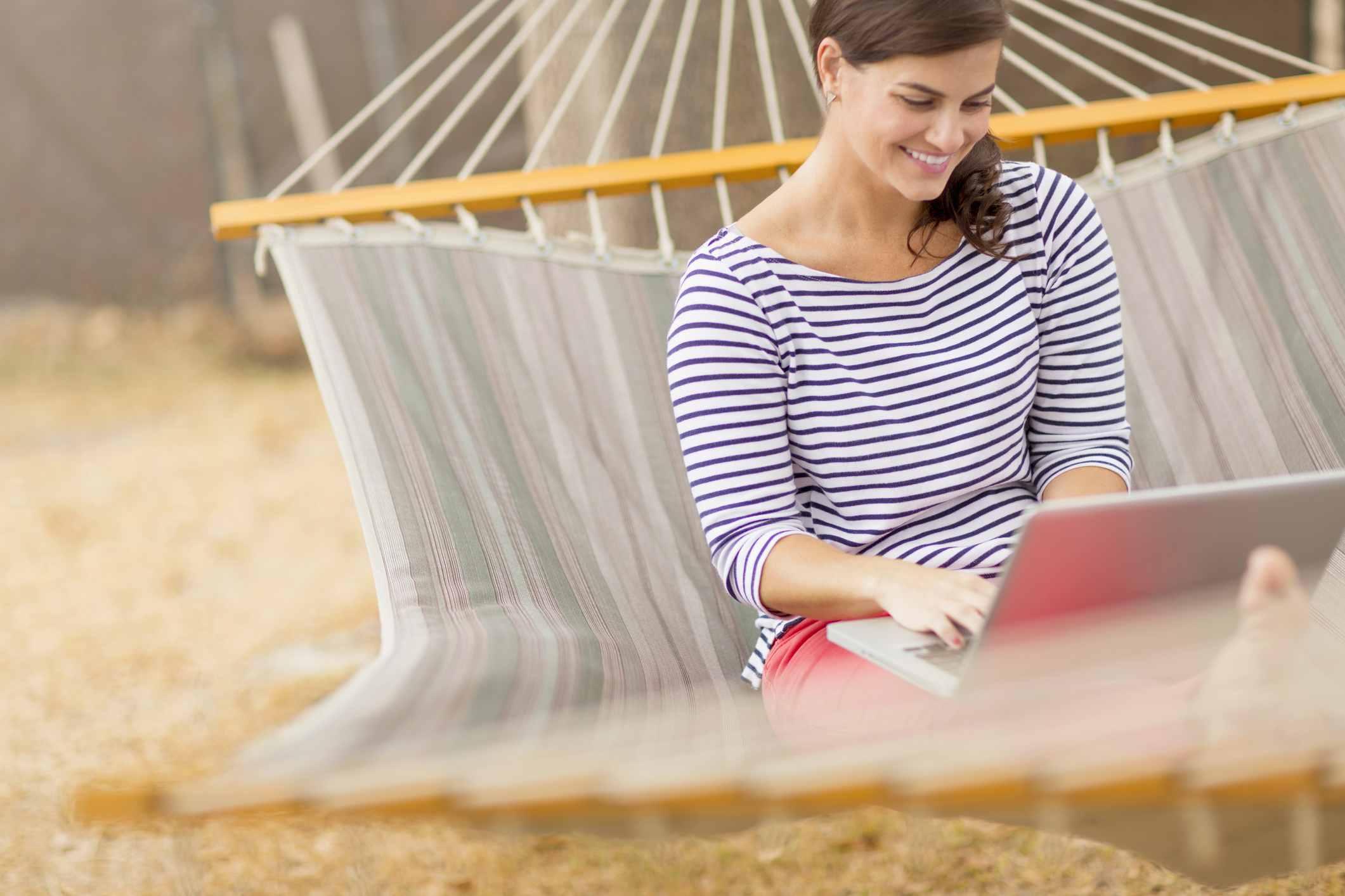 kvinne i hengekøye med PC i fanget, planlegger smart bruk av feriepenger