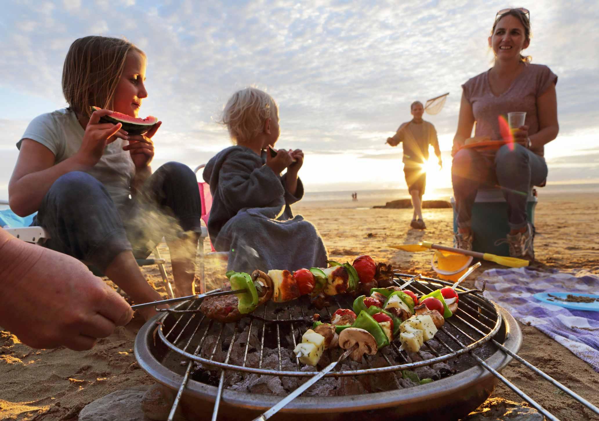 Familie som griller på stranden